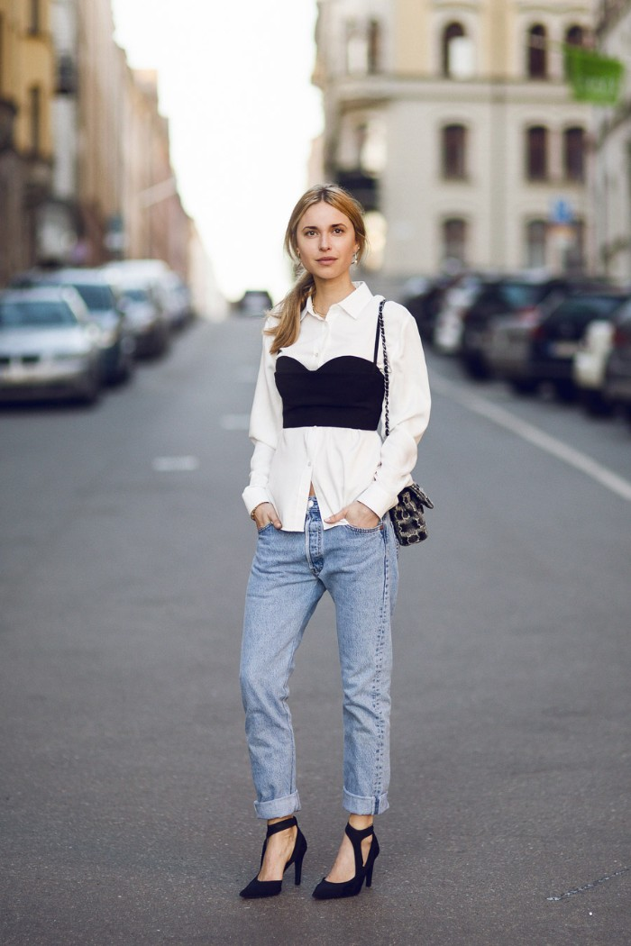light blue jeans, and black high heeled shoes, worn by a young blonde woman, with a black, bustier style bralette, worn over a plain white shirt, bralette outfit ideas