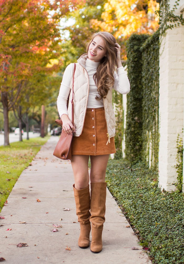 beige suede boots, and a button up mini skirt, in a similar color, worn with a white polo neck jumper, and a quilted cream gilet, thanksgiving outfits for women, on a smiling blonde woman, with long hair