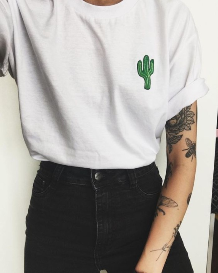 90s grunge fashion, oversized white t-shirt, with a small green cactus applique detail, worn tucked into black skinny jeans