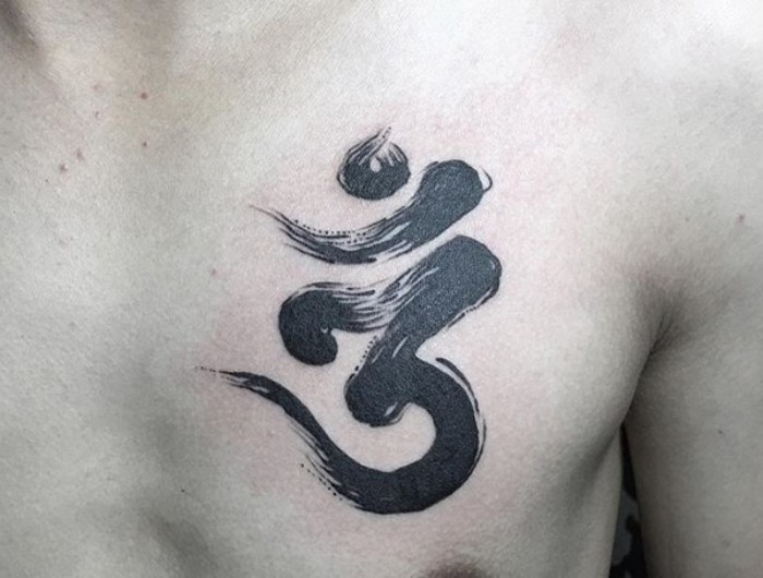 sacred hinduist sound om, spiritual symbol with a caligraphic design, tattooed on a man's chest, small meaningful tattoos, done in black ink