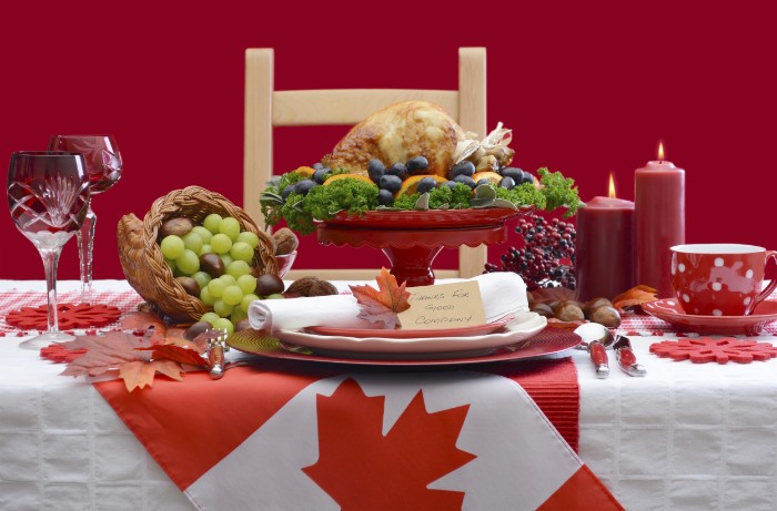 flag of canada, decorating a table, with a roasted turkey, grapes and two lit candles, thanksgiving message to employees, plates and wine glasses, a coffee cup and a saucer
