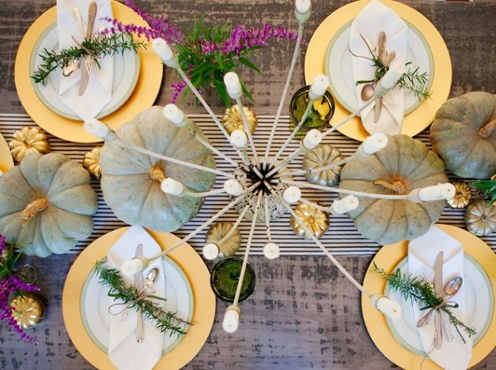 multiple white candles, in an a candle holder, placed near four pale grey pumpkins, on a table with a grey tablecloth, thanksgiving tablescape, with white and gold dishes, white napkins and silver cutlery