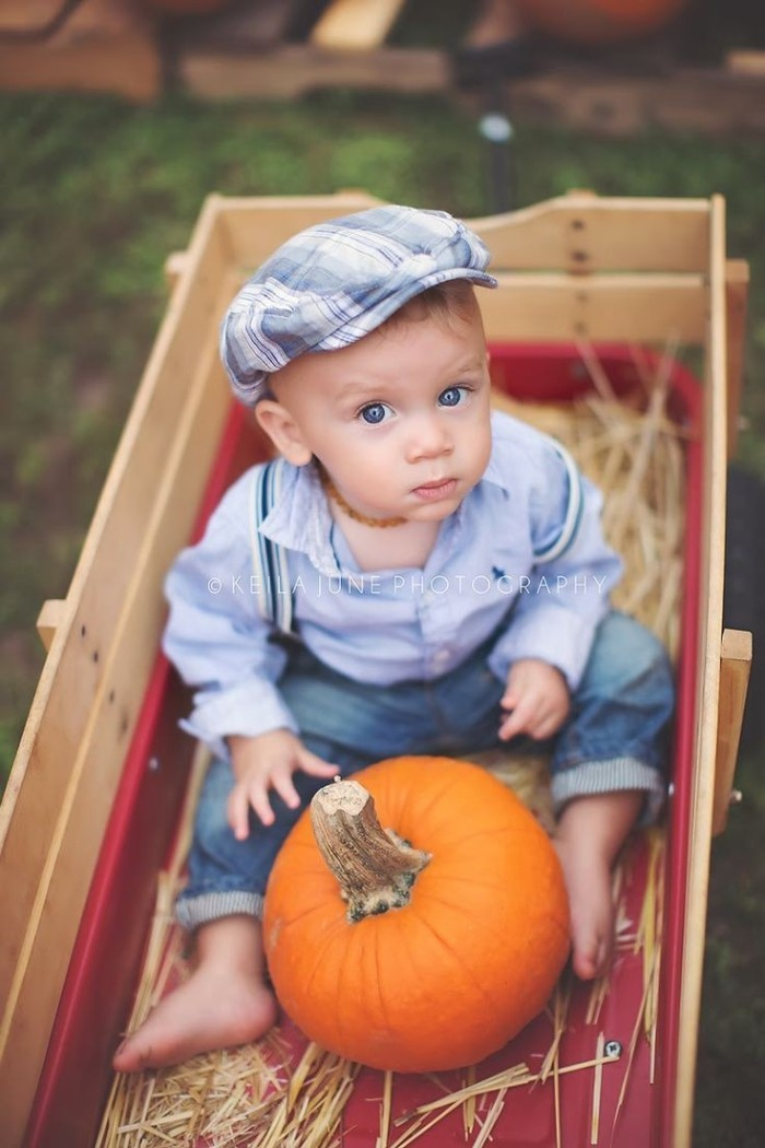 newsboy cap in white and blue, worn by a small baby boy, dressed in jeans with suspenders, and a pale blue shirt, baby thanksgiving outfits, sitting in a wooden cart, with straw and a pumpkin