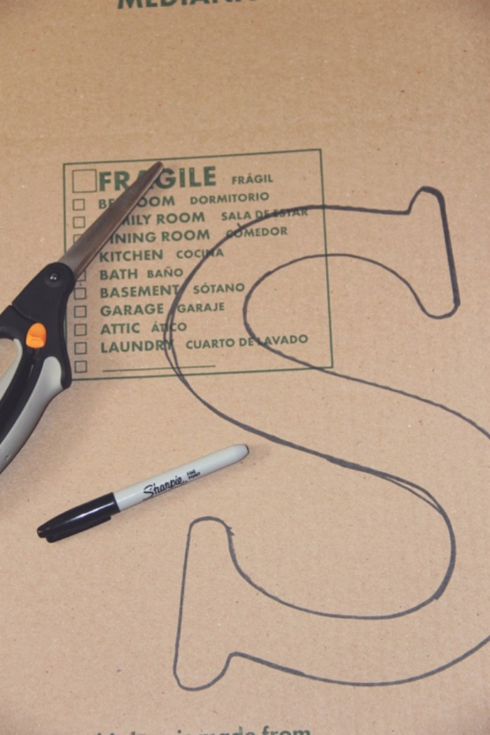 pair of scissors, and a black marker, placed on top, of a piece of beige cardboard, teenage girl room ideas, with the letter s, drawn on it in black