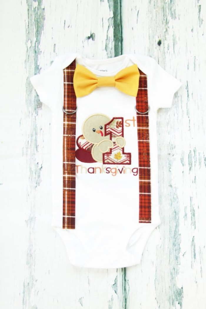 baby's first thanksgiving outfit, white onesie with short sleeves, featuring a cartoon turkey print, with the inscription 1st thanksgiving, yellow bow tie, and faux suspenders