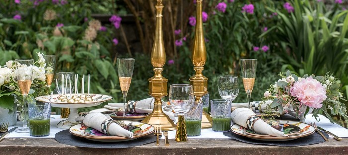 50th birthday party ideas, table with colorful plates, napkins and half-filled champagne flutes, decorated with flowers and two gold candle holders, in a garden with multiple green plants