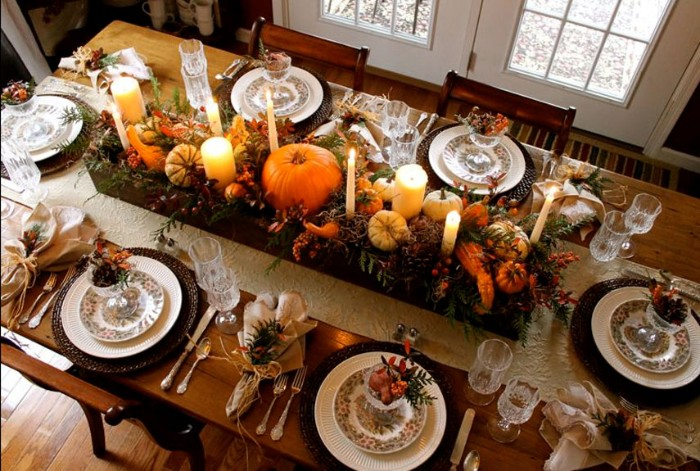 table set for six, and decorated with a long and narrow wooden crate, containig pumpkins and candles, gourds and fruit, and leaves in different colors, thanksgiving centerpiece, on a rectnagular wooden table