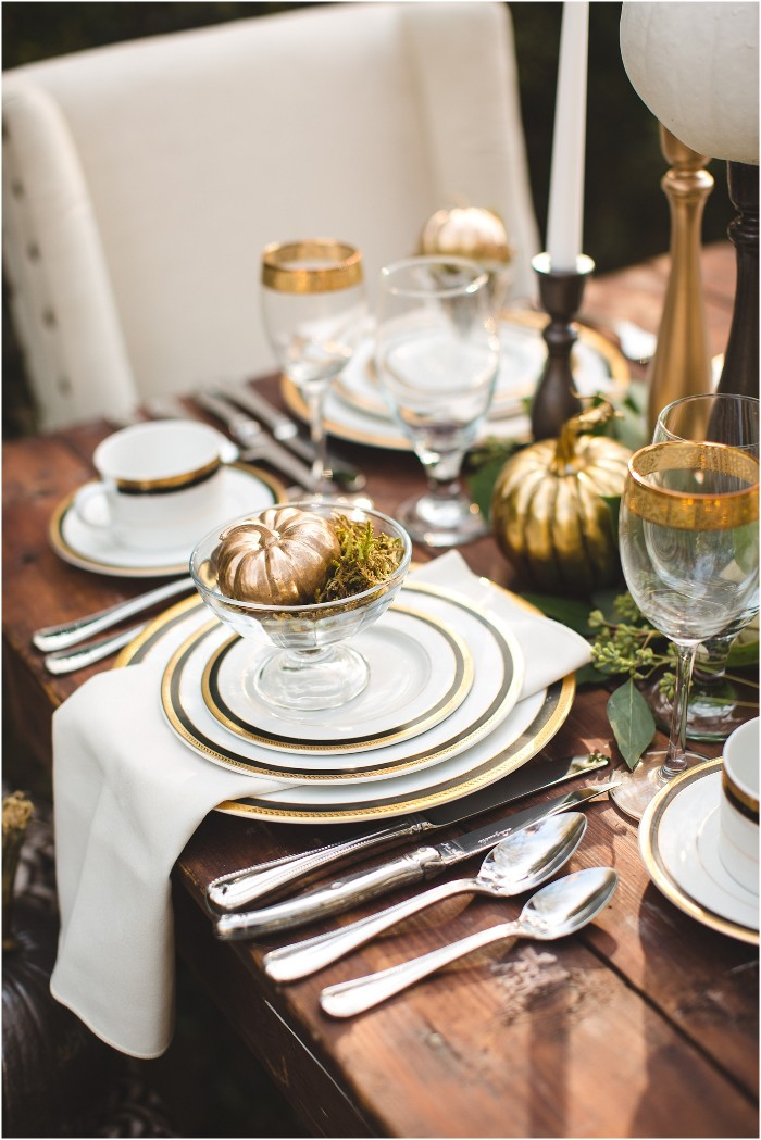 thanksgiving table decorations, spray painted gold ornamental pumpkin, placed in a glass bowl, decorated with moss, on top of three stacked plates, with a white napkin between them