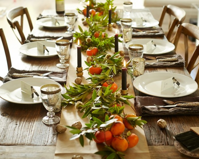 rustic style table, decorated with clementine leaves and fruit, with thanksgiving dinnerware, white round plates, and gold rimmed glasses, lit dark green candles
