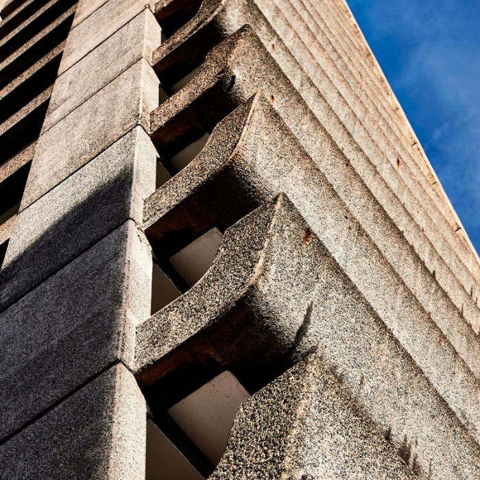 terraces made of concrete, on a tall building, seen in close up, brutalist architecture, blue sky in the background