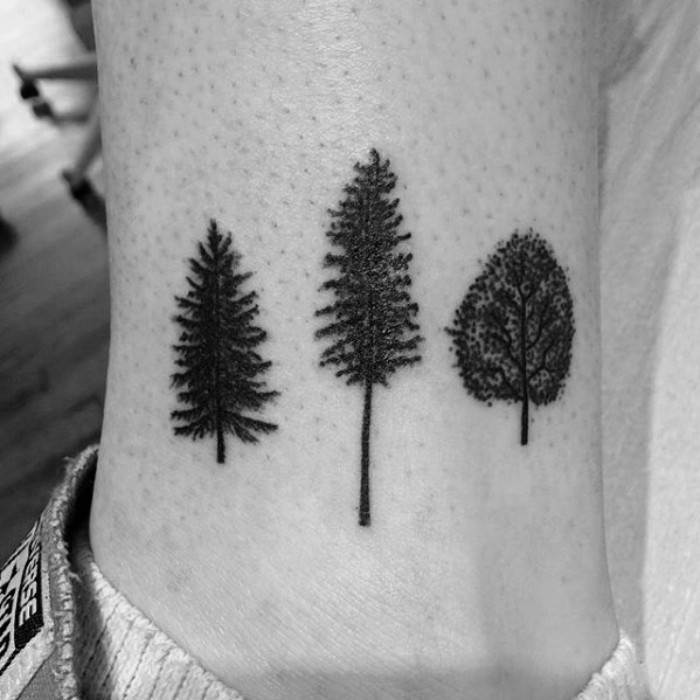 three small tattooes of different trees, done in black ink, on a man's ankle, seen in close up