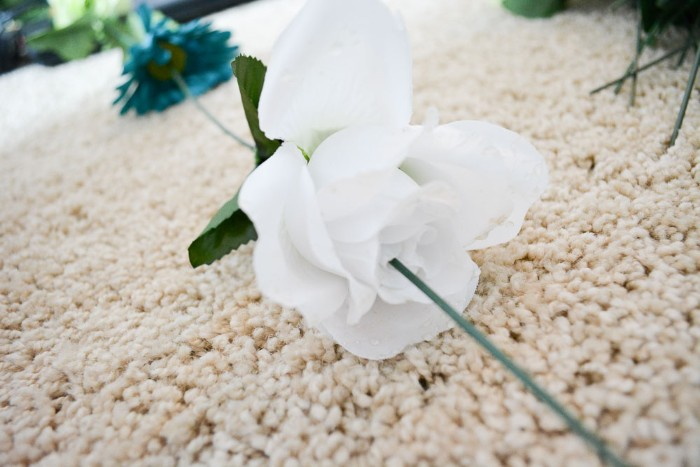 extreme close up, of a fake white rose, with a green plastic stem of another faux flower, stuck on its top, diys for your room, making a flower wall decoration