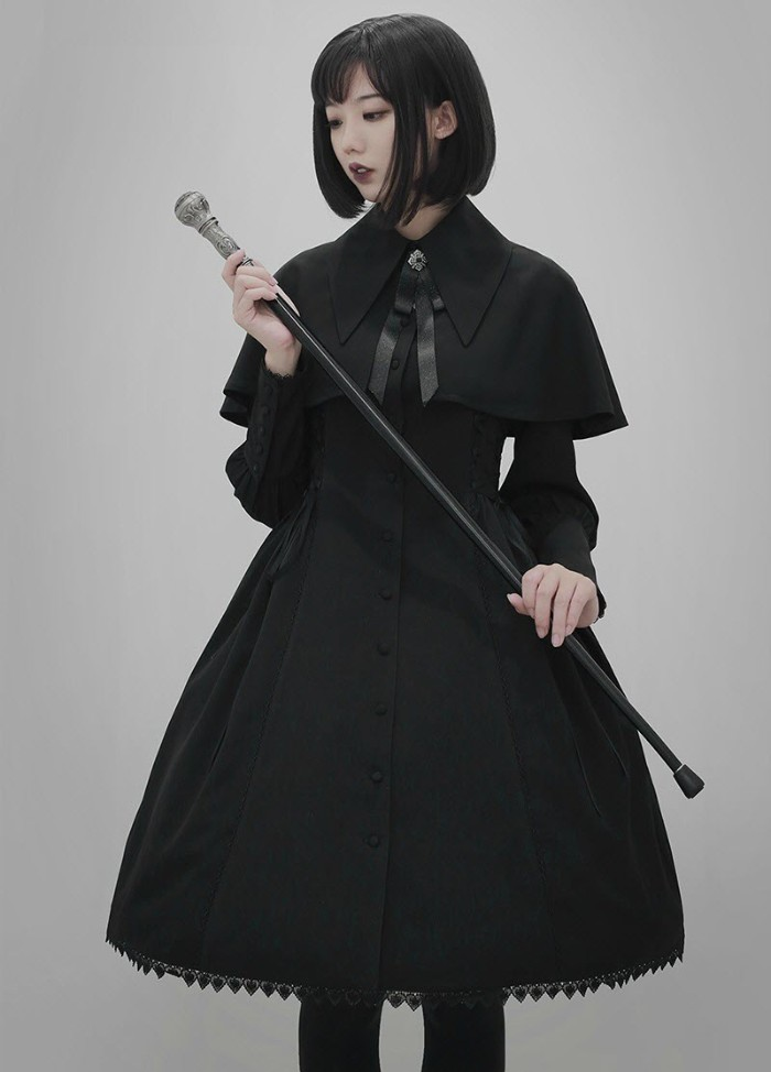 kane held by a young pale woman, dressed in a black military style, gothic lolita dress, with a shoulder cape