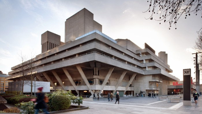 denys lasdun's national theatre, in london england, brutalist art, large multi-storey building, made of grey concrete, and supported by several concrete beams