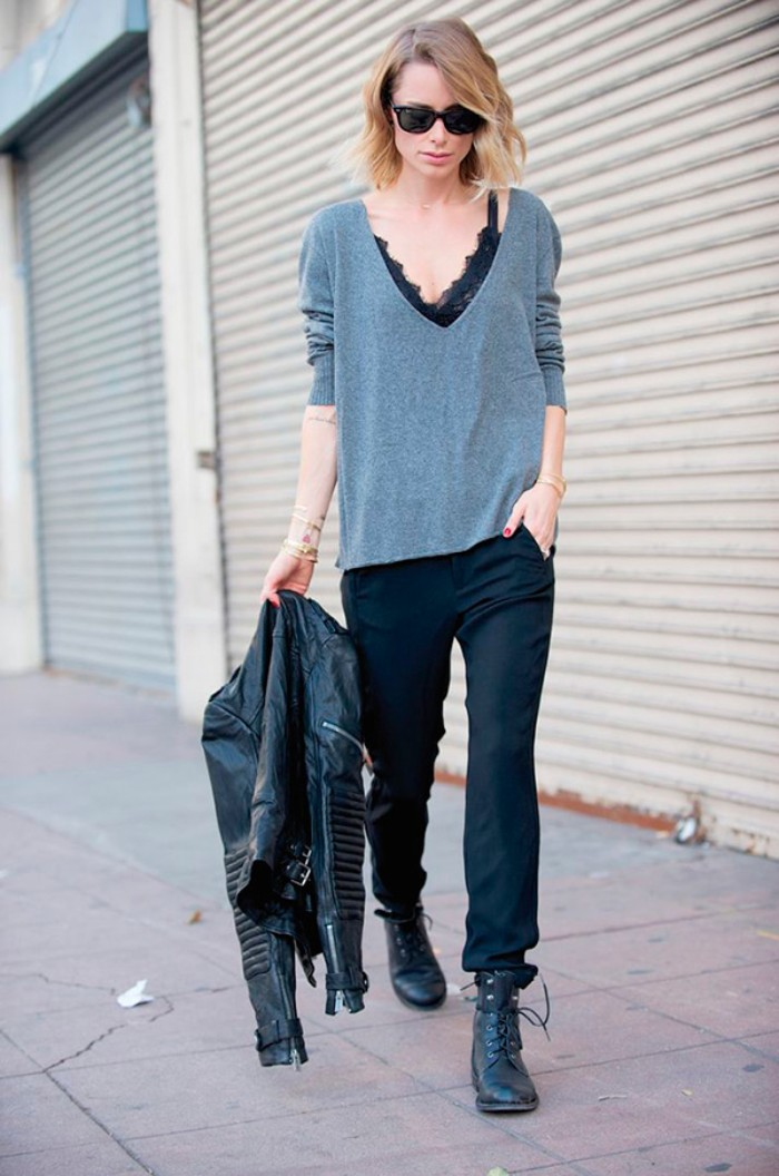 biker leather jacket in black, held by a slim brunette woman, dressed in black trousers, black combat boots, a black lace bralette, and a baggy grey v-neck top, bralette outfit