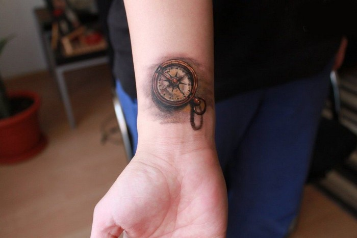 forearm tattoos, compass in yellow and grey, seen in close up, tattooed on a person's wrist