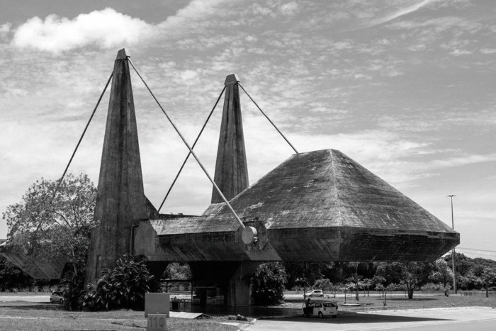 centro de exposiçõesdocentroadministrativo daBahia, in bahia brazil, large dark concrete structure, suspended in the air, by big metal ropes, tied to two columns