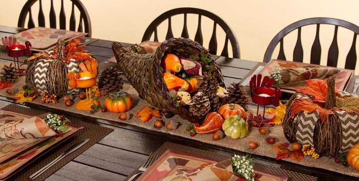 wicker decorations shaped like two pumpkins, and a cornucopia, filled with gourds, pinecones and nuts, on a dark brown wooden table, thanksgiving tablescape, acorns and orange fall leaves