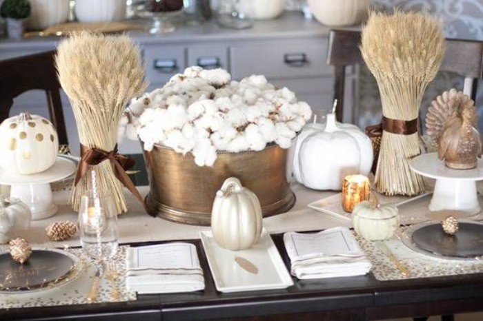 two bunches of dried wheat stalks, tied with brown ribbons, and placed in clear vases, on either side of a brass pot, filled with cotton branches, thanksgiving table ideas