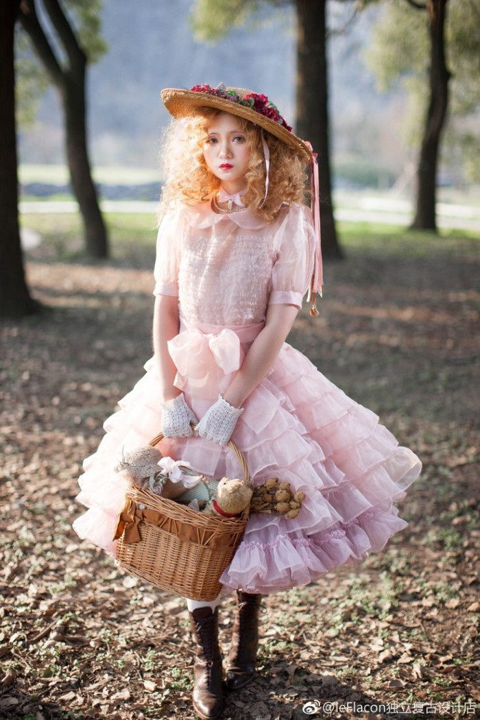 doll-like lolita style outfit, featuring a voluminous, frilly pale pink dress, a straw hat decorated with faux flowers, and a basket bag, worn by a woman with a curly ginger wig, and exaggerated makeup