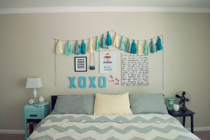 garland with cream, pale blue and turquoise tassels, hanging on a cream wall, decorated with three posters, and other ornaments, bed with three pillows nearby