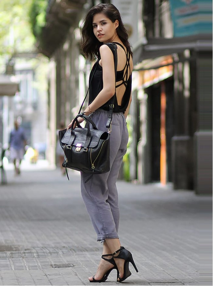 open back top in black, worn over a black bralette, with crossing straps, by a brunette woman, what is a bralette, light grey ankle trousers, black high heel sandals