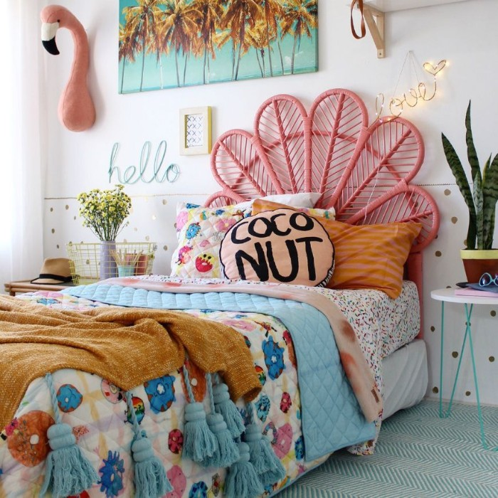 teenage girl room ideas, multicolored bed cover, on a single bed, with a pink, fan-like bed frame, potted plant and decorations nearby