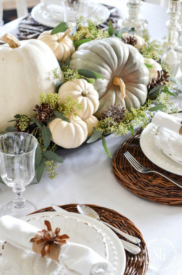 light grey and cream pumpkins, surrounded by purple, and pale green plants, on a table with round, brown wicker table mats, white dishes and napkins, glasses and cutlery, cheap centerpiece ideas