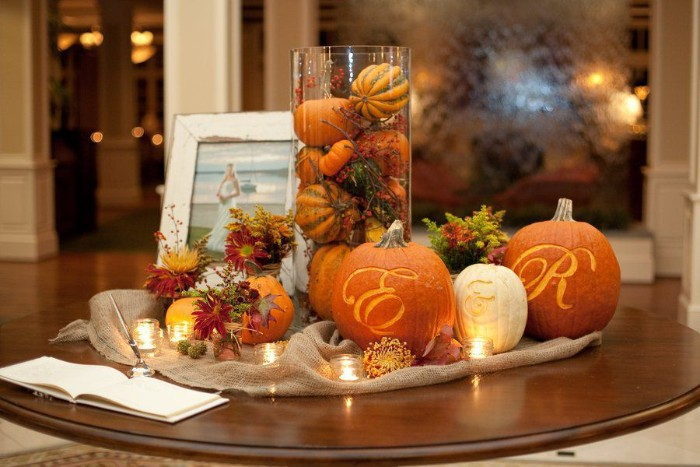 tea lights and flowers, and tiny orange pumpkins, surrounding three bigger pumpkins, with the letters e and r, and the sign & engraved on them, cheap centerpiece ideas, on a round dark brown table