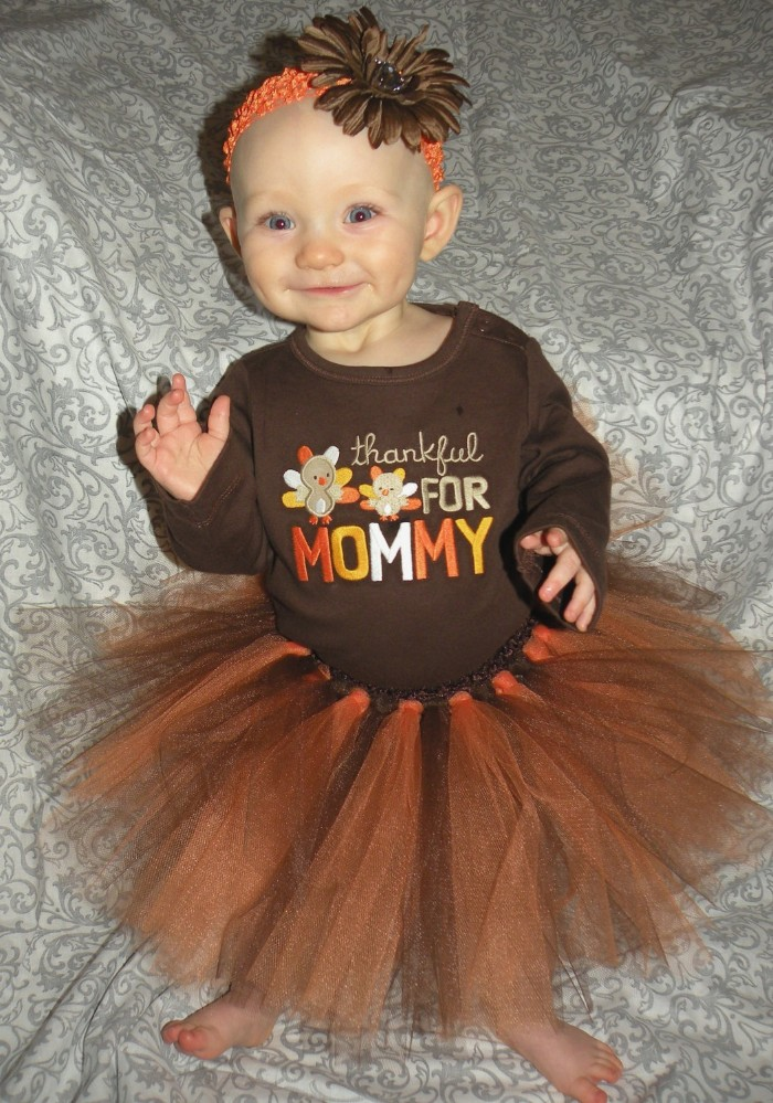 baby girl thanksgiving outfit, brown jumper with orange and beige, yellow and white embroidery, and a brown and orange tutu skirt, on a smiling dimpled baby