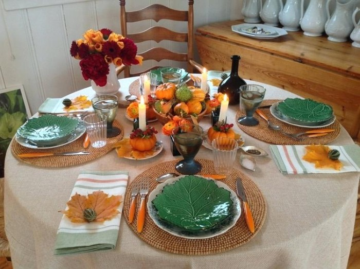green dishes shaped like cabbage leaves, on a round table set for four, cutlery with orange handles, red and orange flowers, pumpkins and fruit