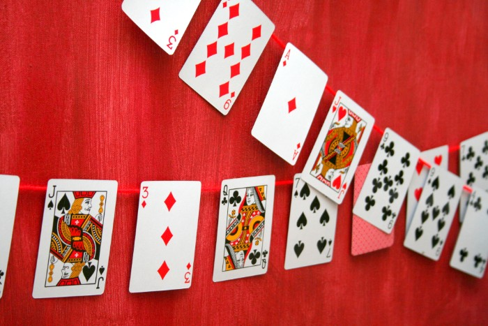 two garlands made from playing gards, stuck onto pieces of red thread, and hung on a red curtain, 50th birthday party ideas for men, poker night theme