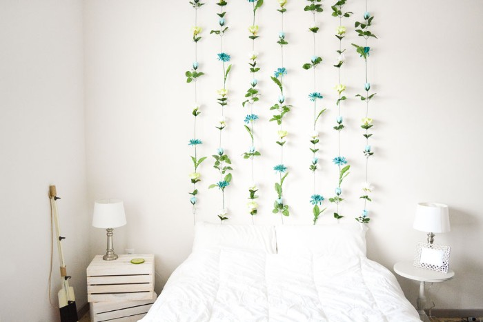 bright room with white walls, a white bed, and two bedside tables, diys for girls, featuring a wall decoration, made from multiple fake flowers, stuck together to form seven columns