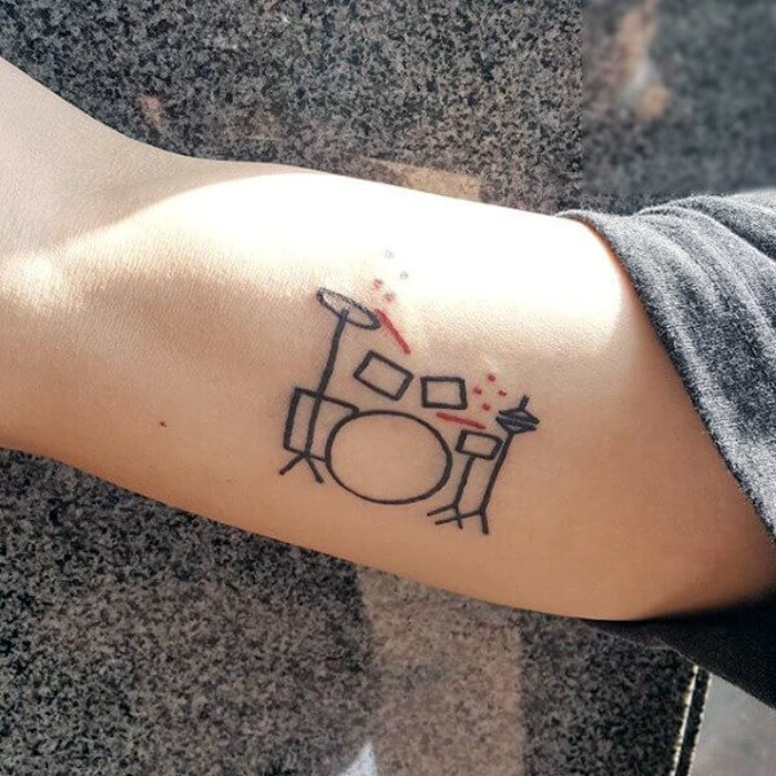 doodle tattoo in black and red, depicting a drum kit, cool arm tattoos, done on a person's upper arm