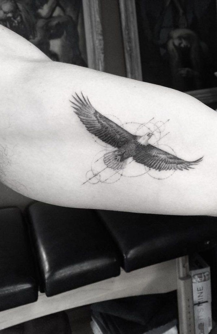 bald eagle flying, decorated with circles and thin arrows, tattoed on a man's arm, bravery and new beginnings, tattoos with deep meaning, deep meaning tattoos for guys