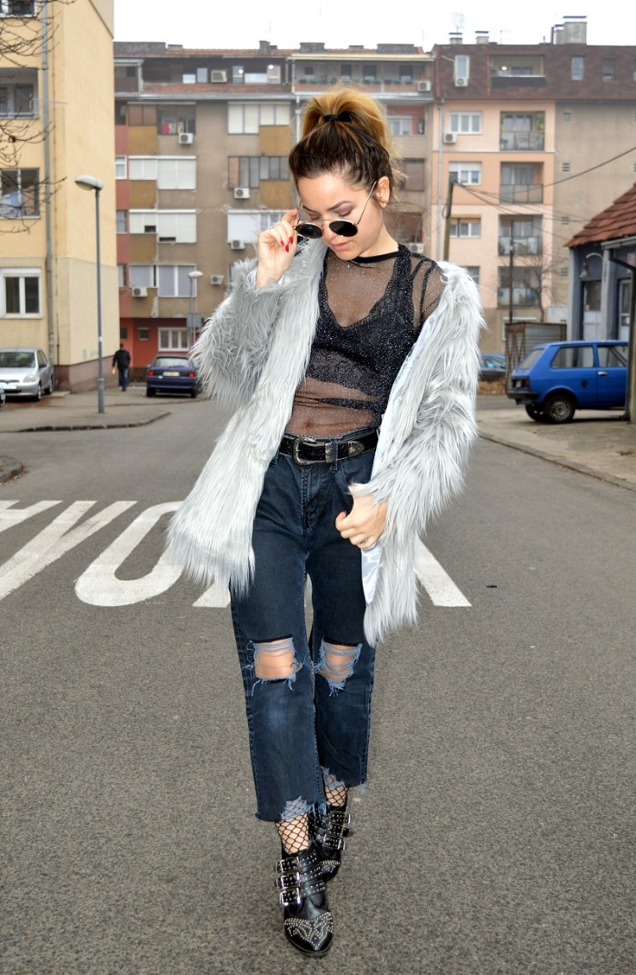 what is a bralette, woman in a grey, faux fur coat, ripped dark blue, wide fit ankle jeans, a sheer black top, and a black bralette