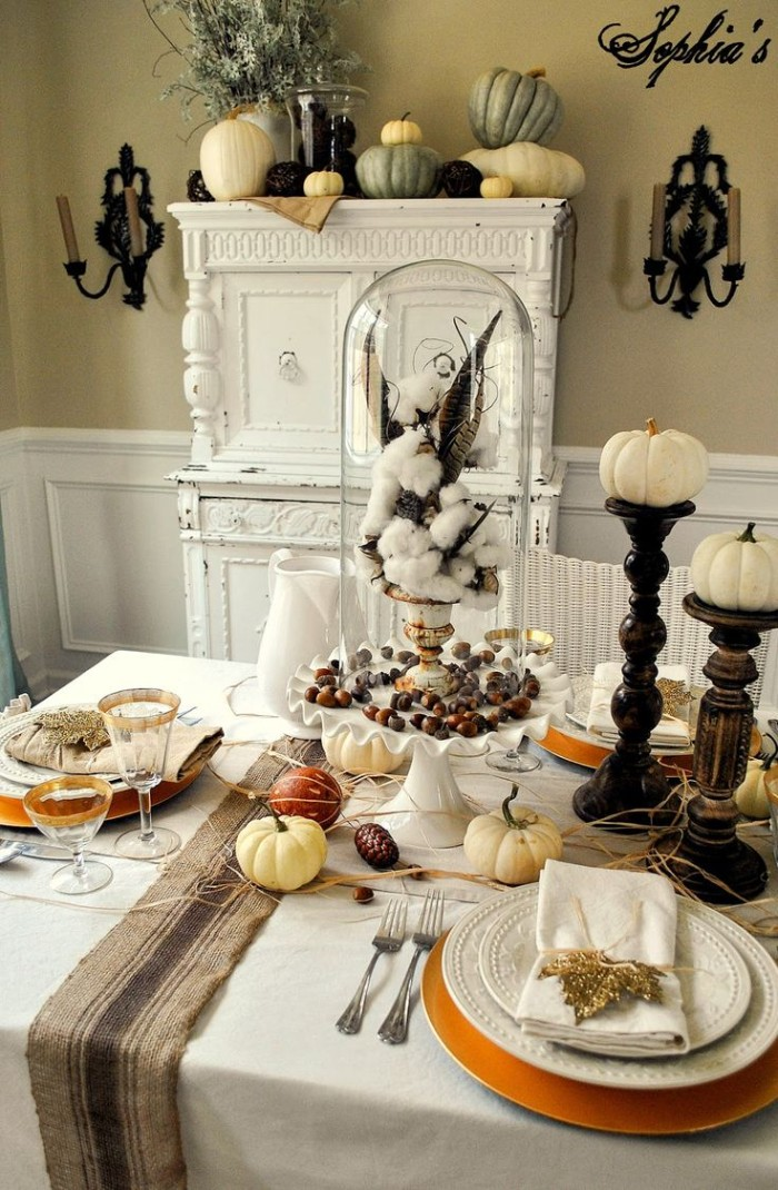 branch of cotton, and brown spotted feathers, in a white and gold vase, placed on top of a white dish containing acorns, thanksgiving centerpiece, pumpkins and a pinecone nearby