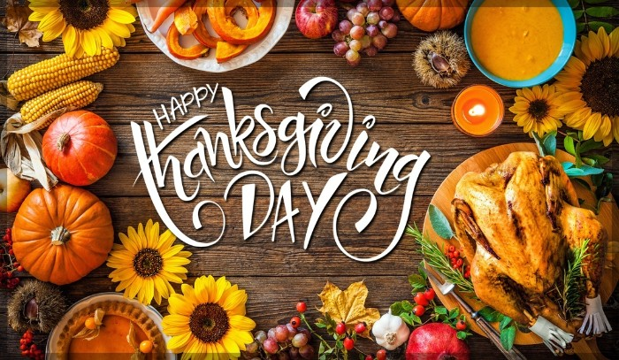sunflowers and ears of corn, roasted turkey and other dishes, a candle and some grapes, on a wooden surface, with the words happy thanksgiving day overimposed in white
