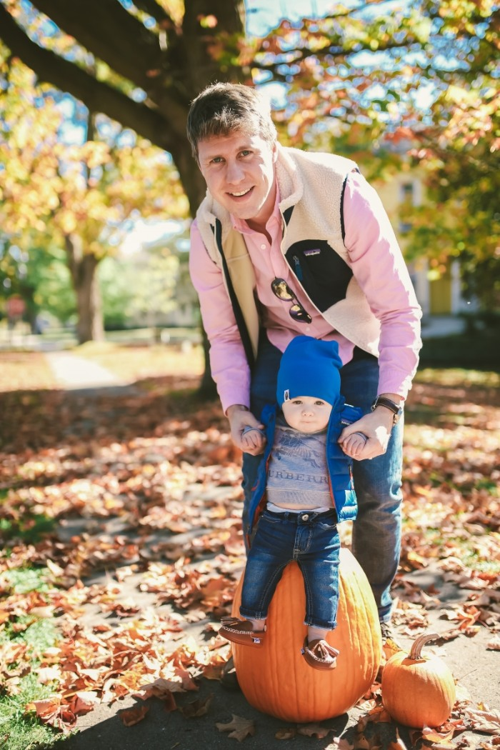 man dressed in a light pink shirt, dark blue jeans, and a pale cream gilet, holding the hands of a small baby, wearing dark blue jeans, a grey t-shirt, blue quilted jacket, and a blue beanie hat, baby thanksgiving outfits for little boys