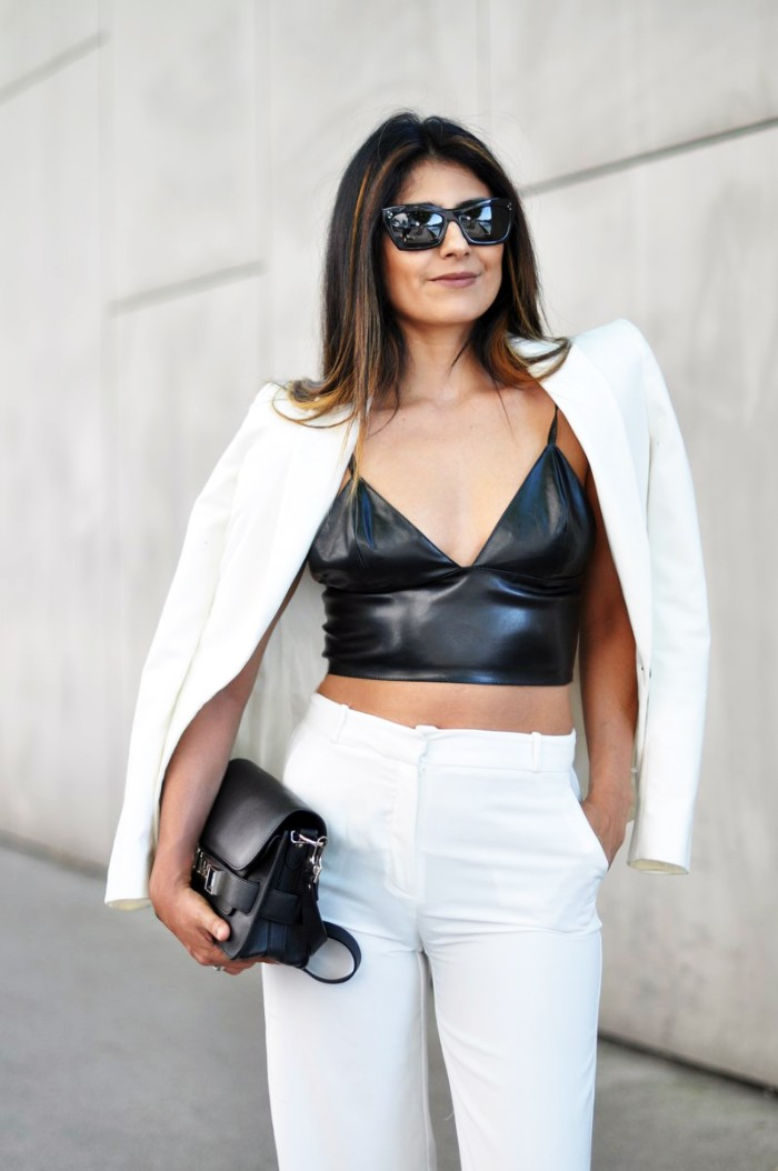 leather look bralette in black, white trousers and a white blazer, worn by a smiling brunette woman, with dark sunglasses, how to wear a bralette, small black bag