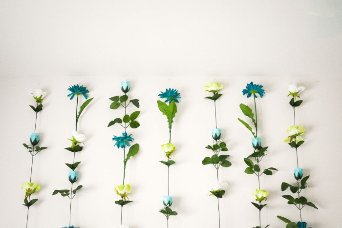 seven columns made of faux flowers, in teal and white, light yellow and pale blue, with long green stems, stuck together, diys for girls, attached to a white wall