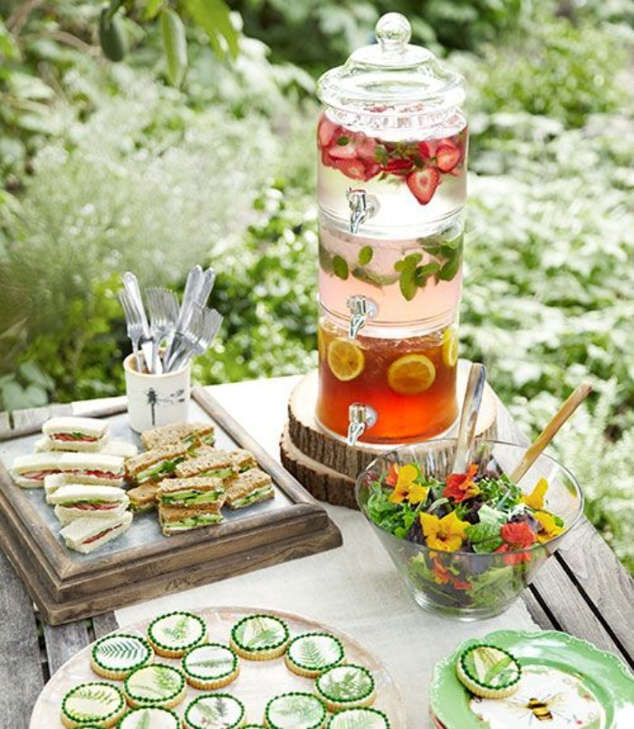 tea garden party, a rustic wooden table, with finger sandwiches, different kinds of lemonade, in a fancy vintage glass dispenser, salad and cookies, 50th birthday party ideas for mom