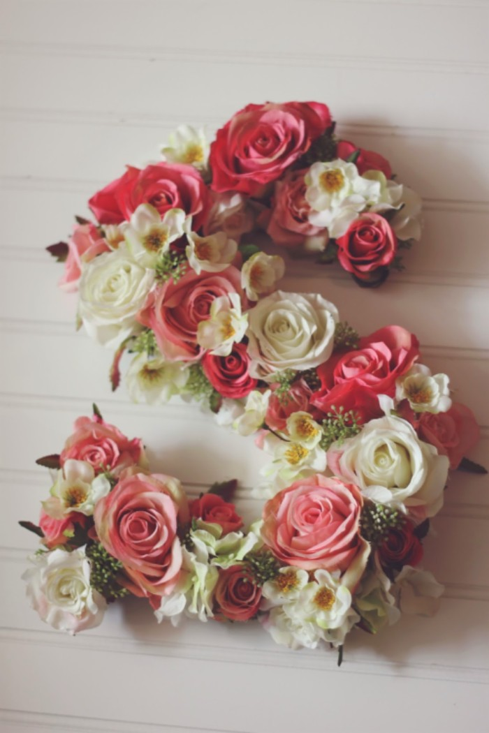 s shape decorated with different faux flowers, pink and white roses, white and yellow blossoms, teenage girl room ideas, on a white surface