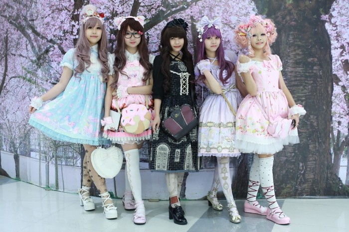 examples of the gothic and sweet lolita styles, five girls in different lolita dresses, pale blue and pink, black and light violet, multicolored with frills and cutesy pattens