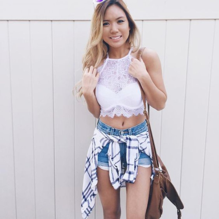striped white flannel shirt, tied around the waist, of a slim young woman, dressed in denim shorts, and a white embroidered bralette