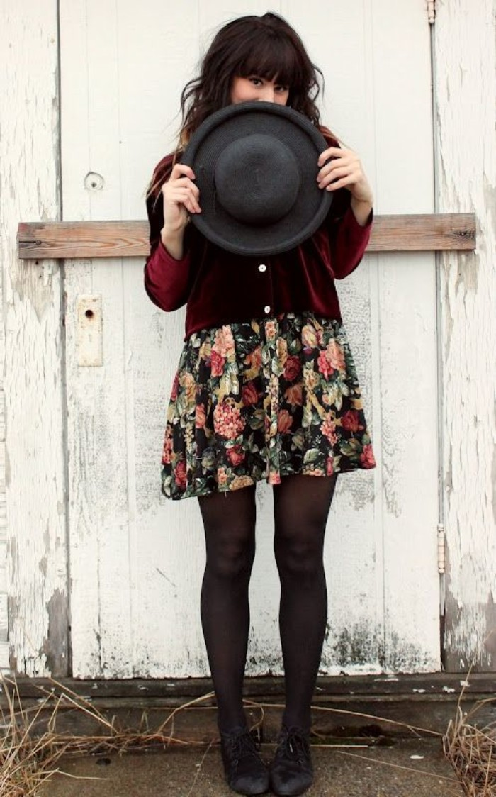 teenage girls thanksgiving outfit, burgundy red velvet cardigan, over a multicolored dress, with a floral pattern, and sheer black tights, black felt hat