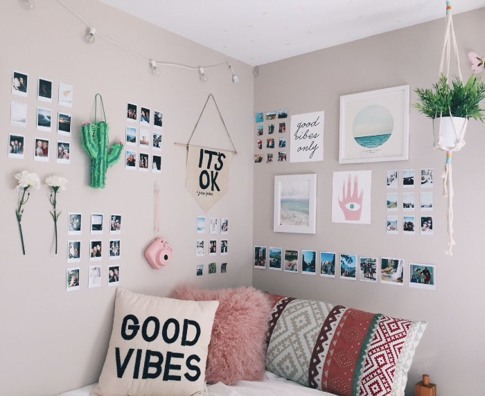 multiple polaroid photos, framed images and flowers, on the beige walls, of a room with a bed, teen bedrooms, three cushions in different colors