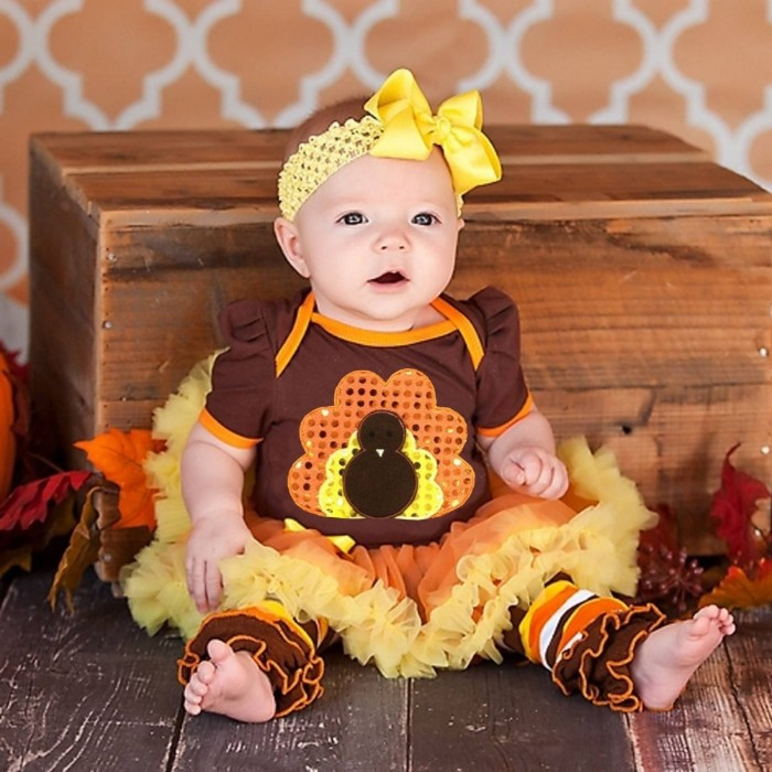 headband with a big yellow bow, worn by a small baby, dressed in a brown, orange and yellow dress, with a sequined turkey motif, and a frilly tutu, baby girl thanksgiving outfit ideas