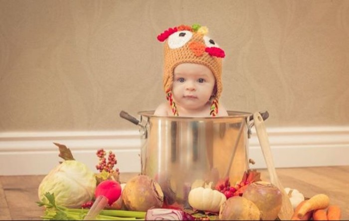 metal cooking pot, containing a small baby, wearing a turkey knitted cap, baby thanksgiving outfits, cabbage and carrots, and other vegetables near the pot
