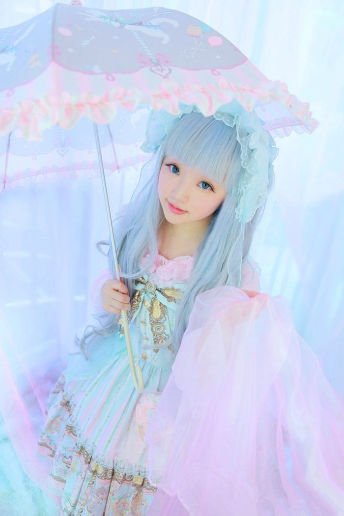 teenage girl in a pale blue wig, dressed in a pastel blue dress, with pastel pink and gold motifs, what is lolita, matching pastel parasol with frills